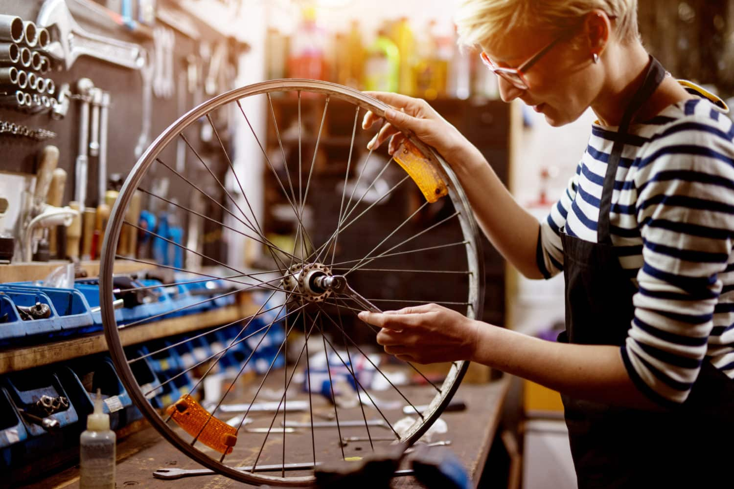 Beautiful focused woman checking bicycle tire with a wrench in the sunny garage. montage assemblage